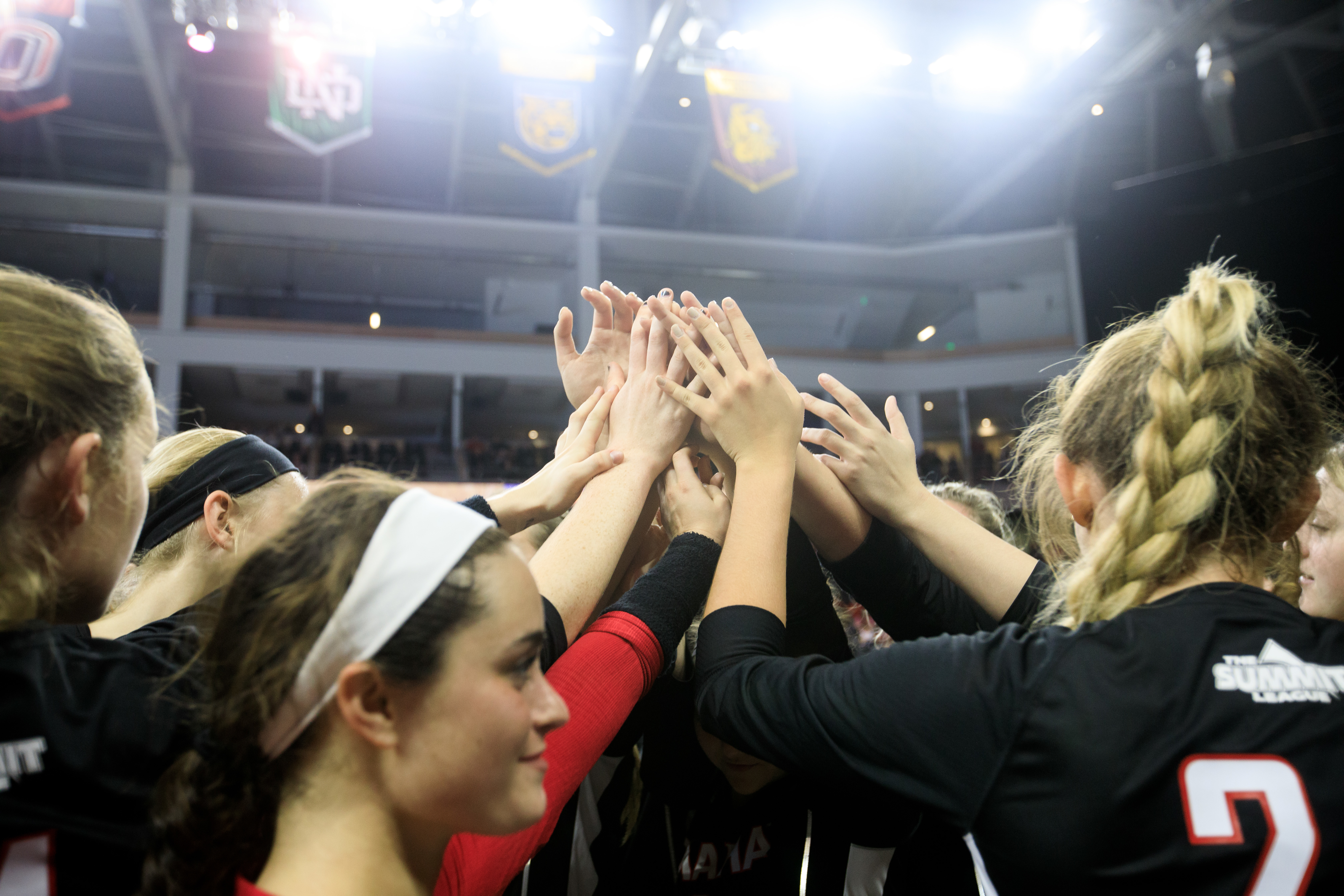 The Maverick volleyball team is in a huddle with their hands together.
