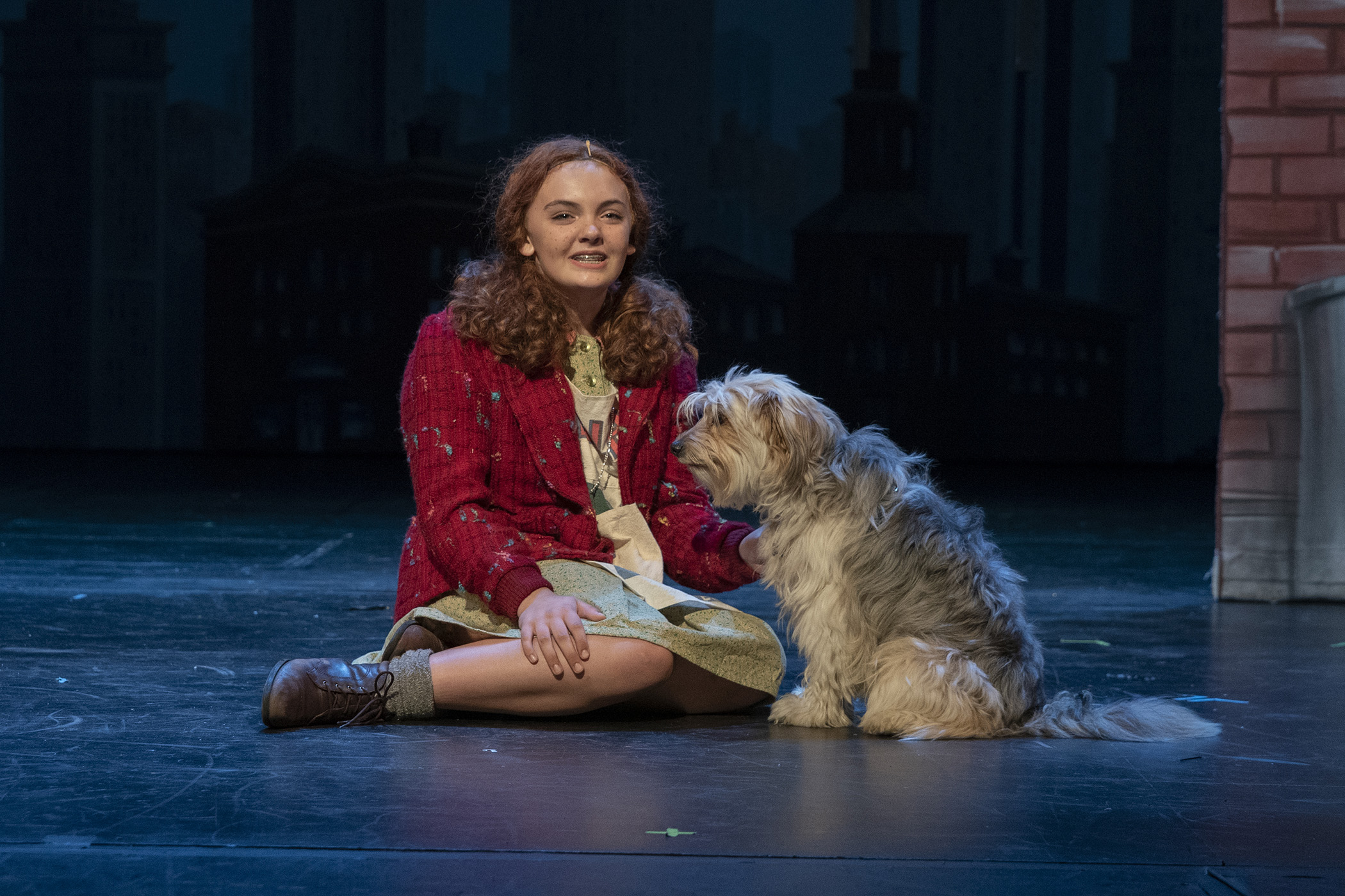 "In the play ""Annie,"" a girl is sitting with a dog."