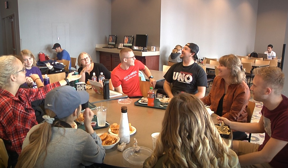 Several college students are sitting at a table eating lunch and using sign language.