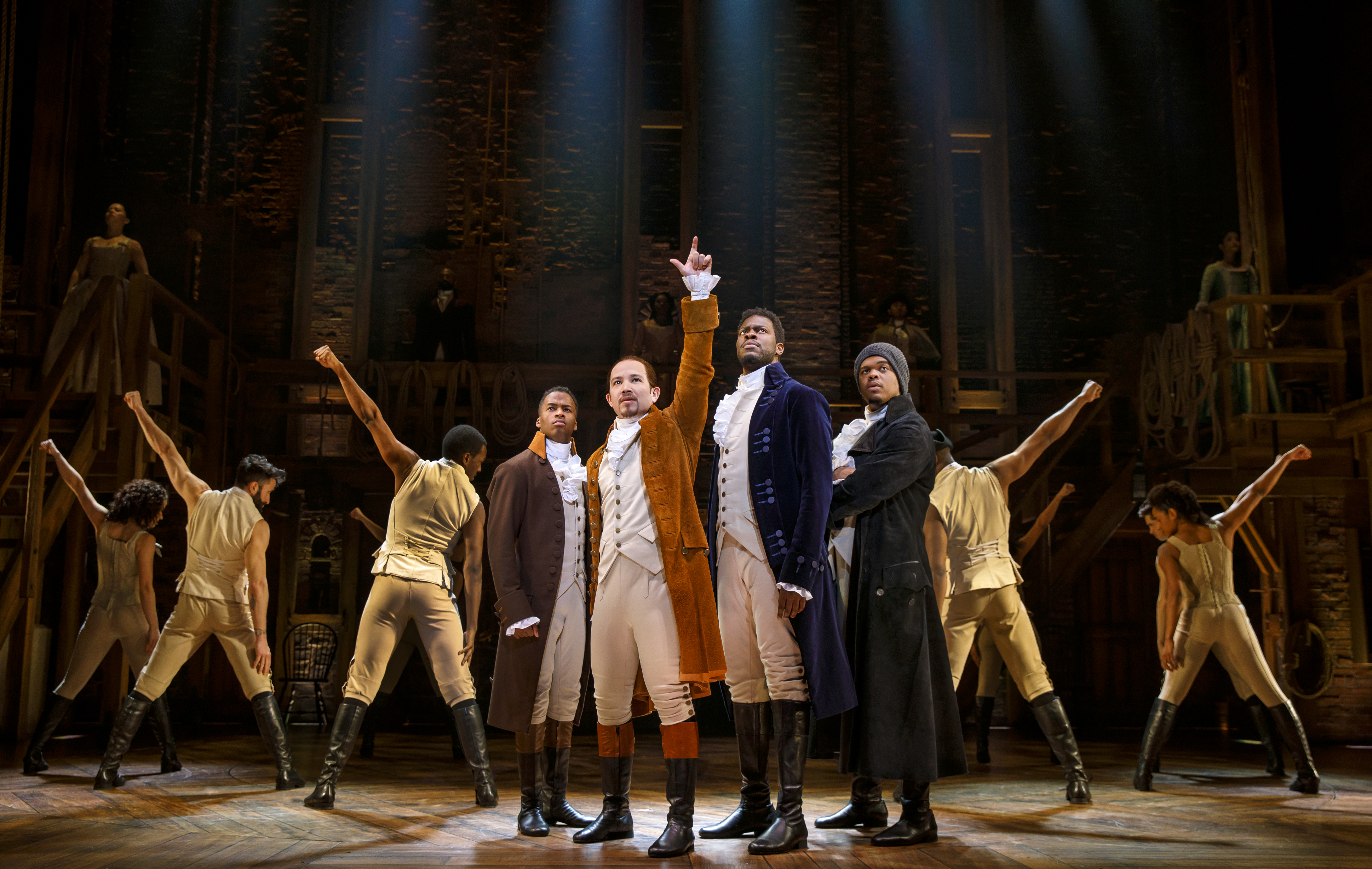 "Several actors perform the musical show ""Hamilton"" on stage."