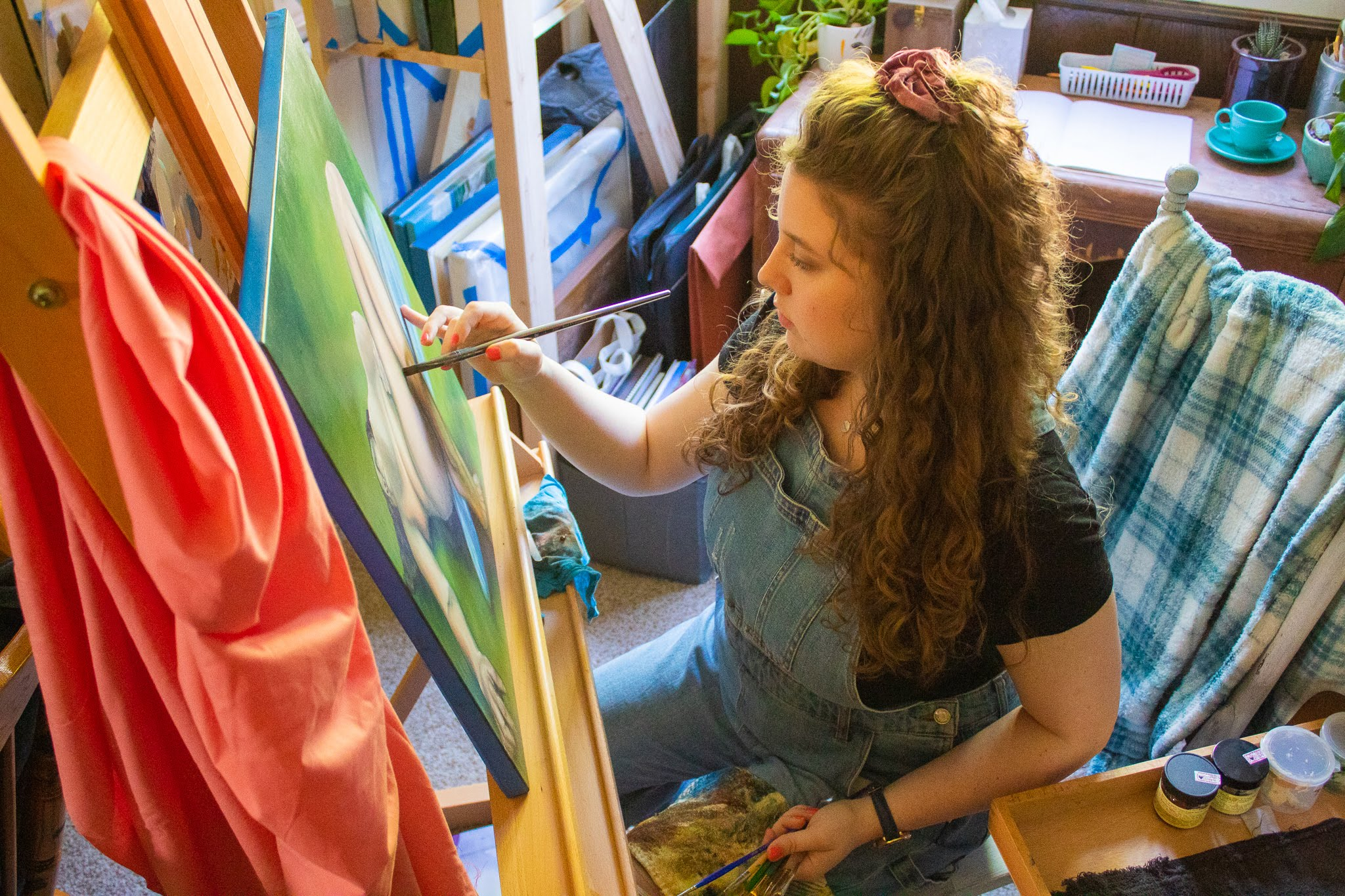 Holly Tharnish, an artist, is sitting in a chair and painting.