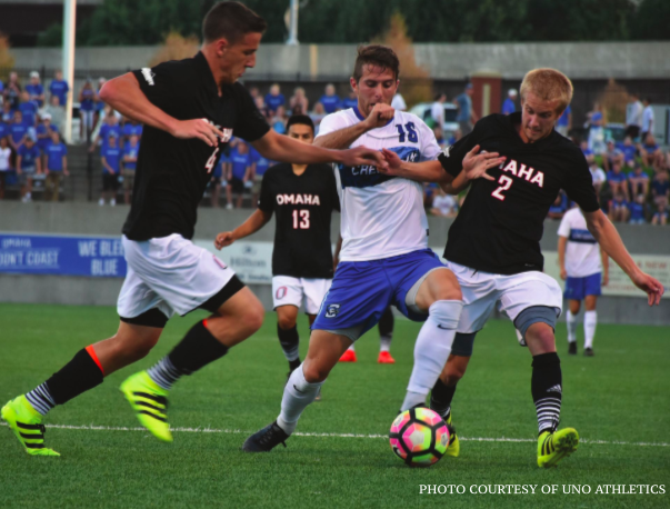 Soccer players from the University of Nebraska at Omaha and Creighton University battle for the ball.