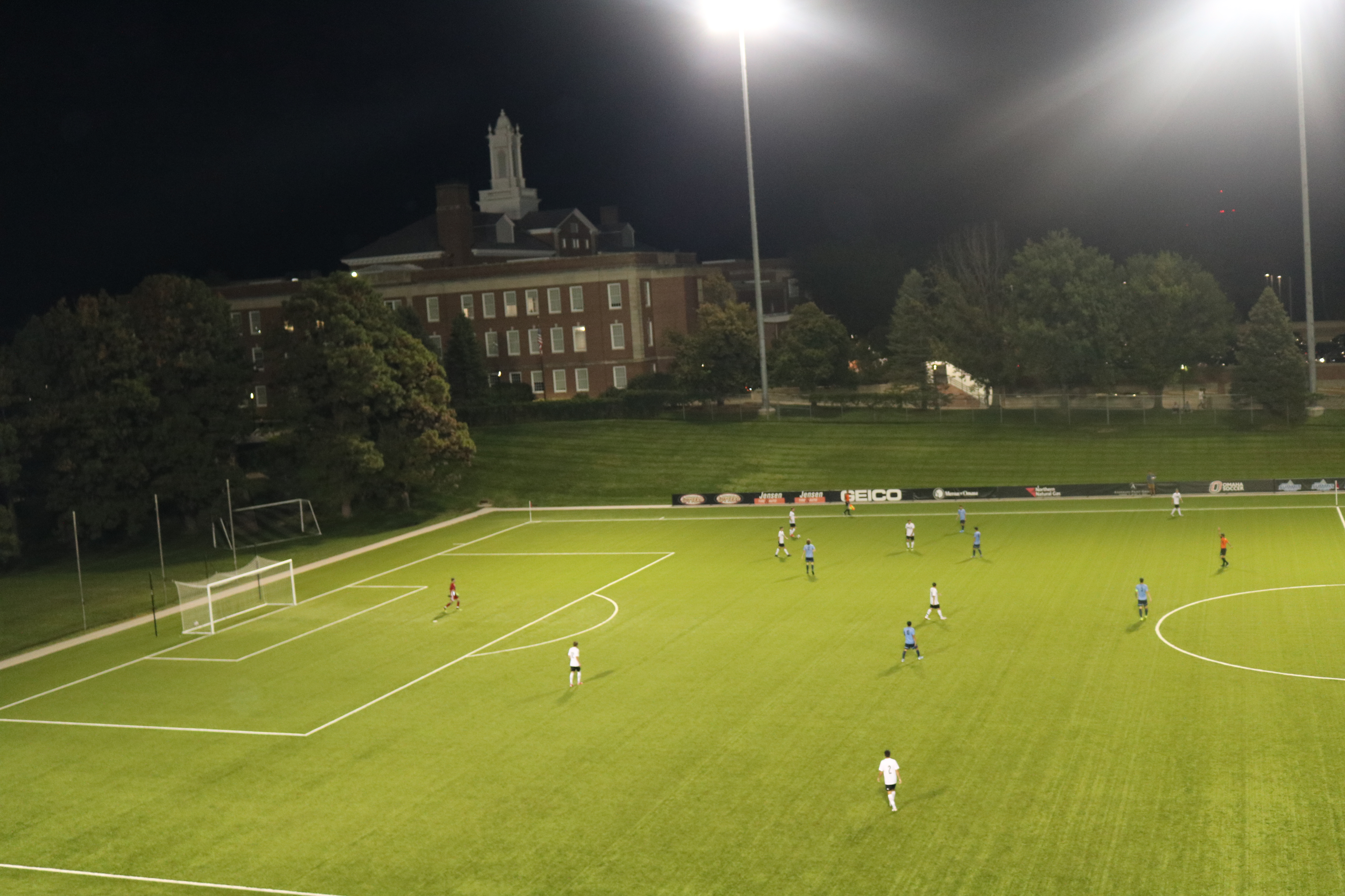 An image of the University of Nebraska at Omaha soccer field with the Arts and Science Hall in the background. Players from both teams are on the field.