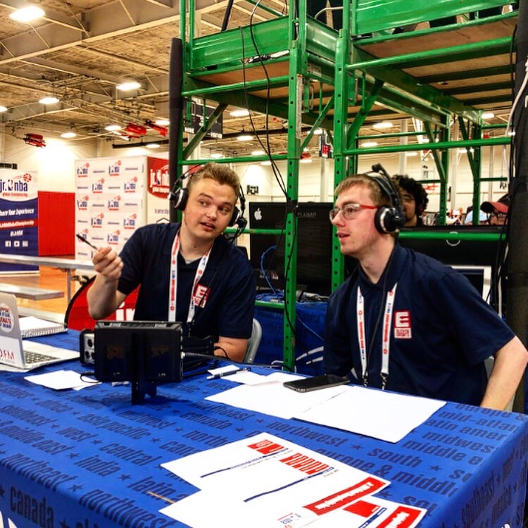 Two college students wearing headsets are working on a radio show.