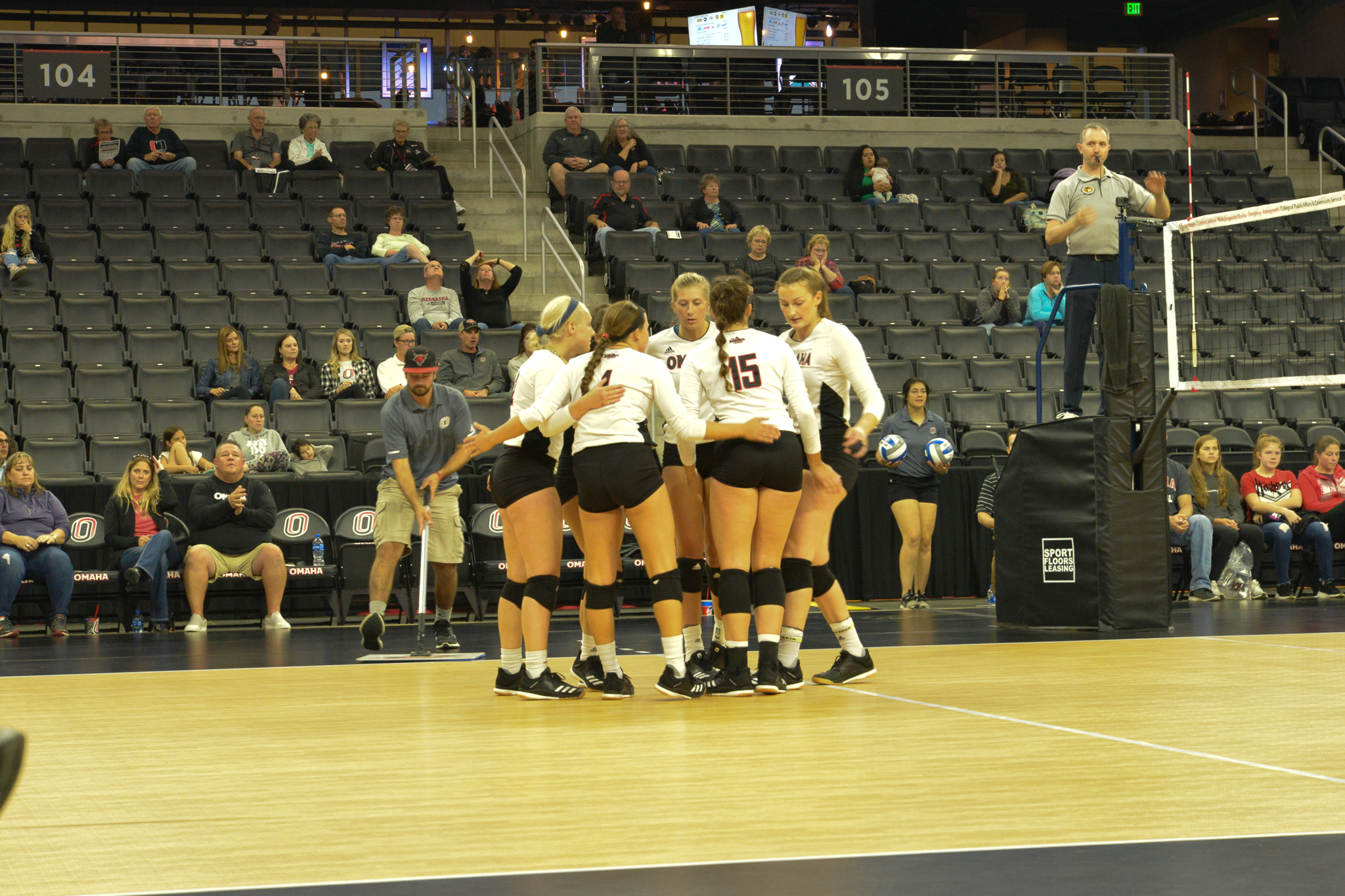 The UNO volleyball team is huddling together at the middle of the court.