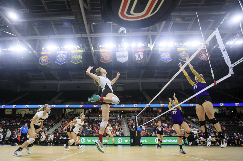 A University of Nebraska at Omaha volleyball player is about to hit the ball over the net.