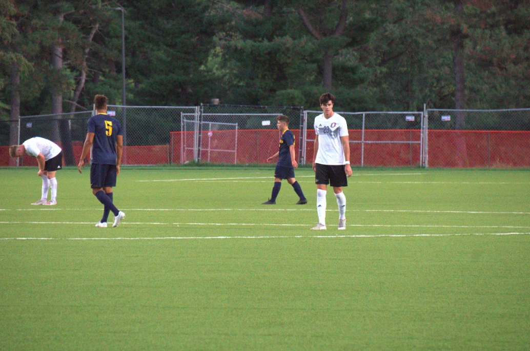 Several soccer players walk across the field