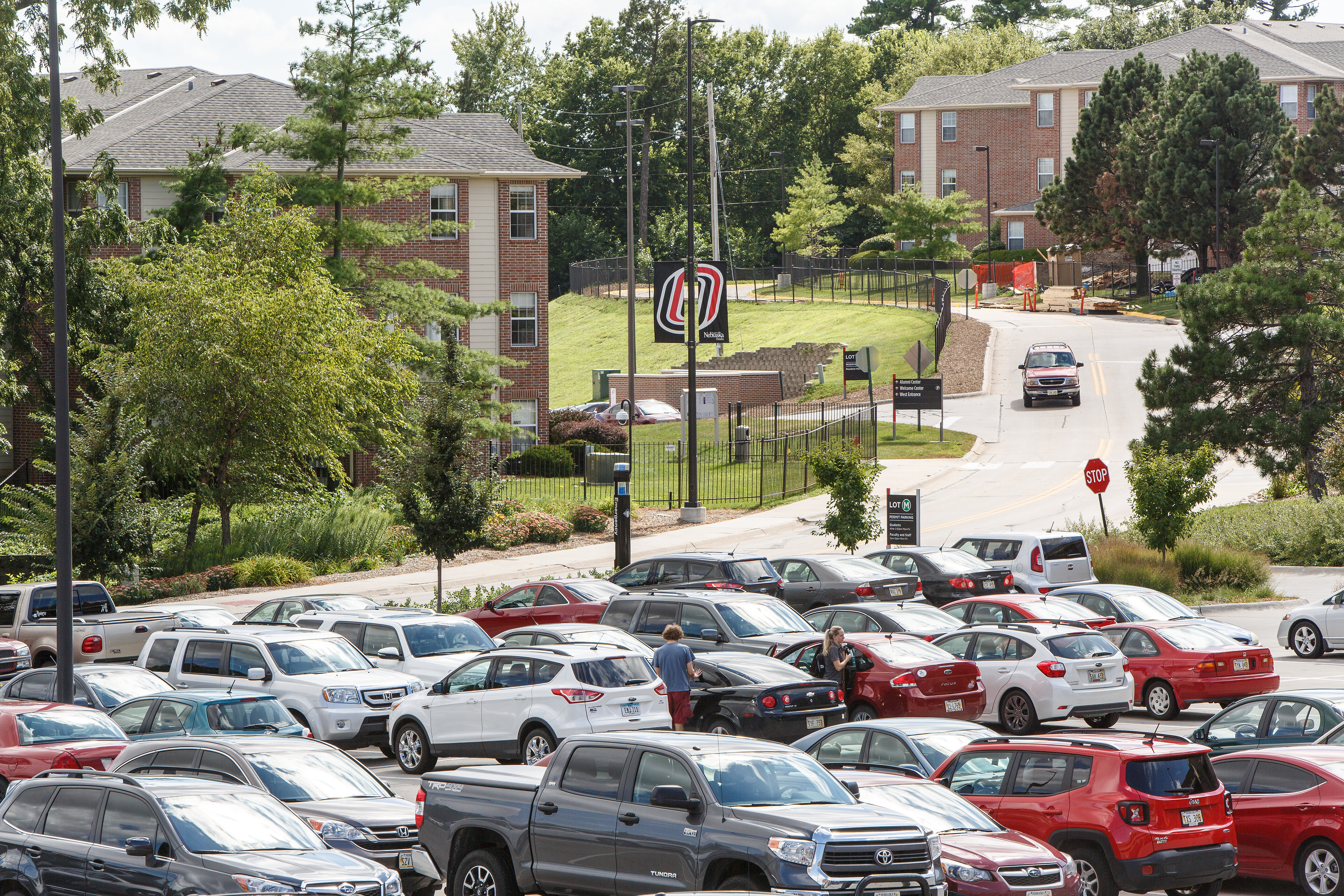 A picture of the UNO campus with many cars in the parking lot outside of the library.