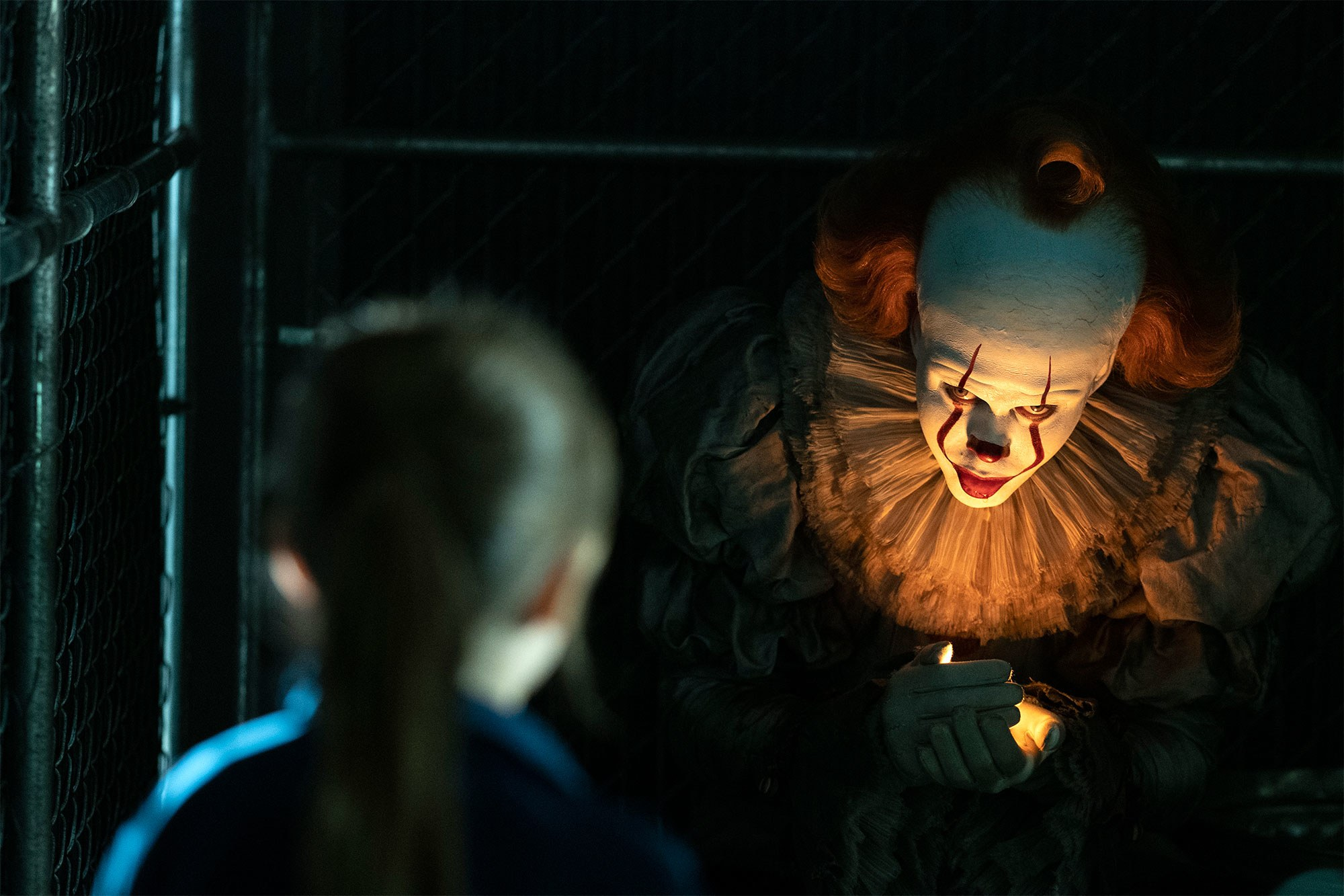 An image from the movie It. A terrifying clown looks at a girl