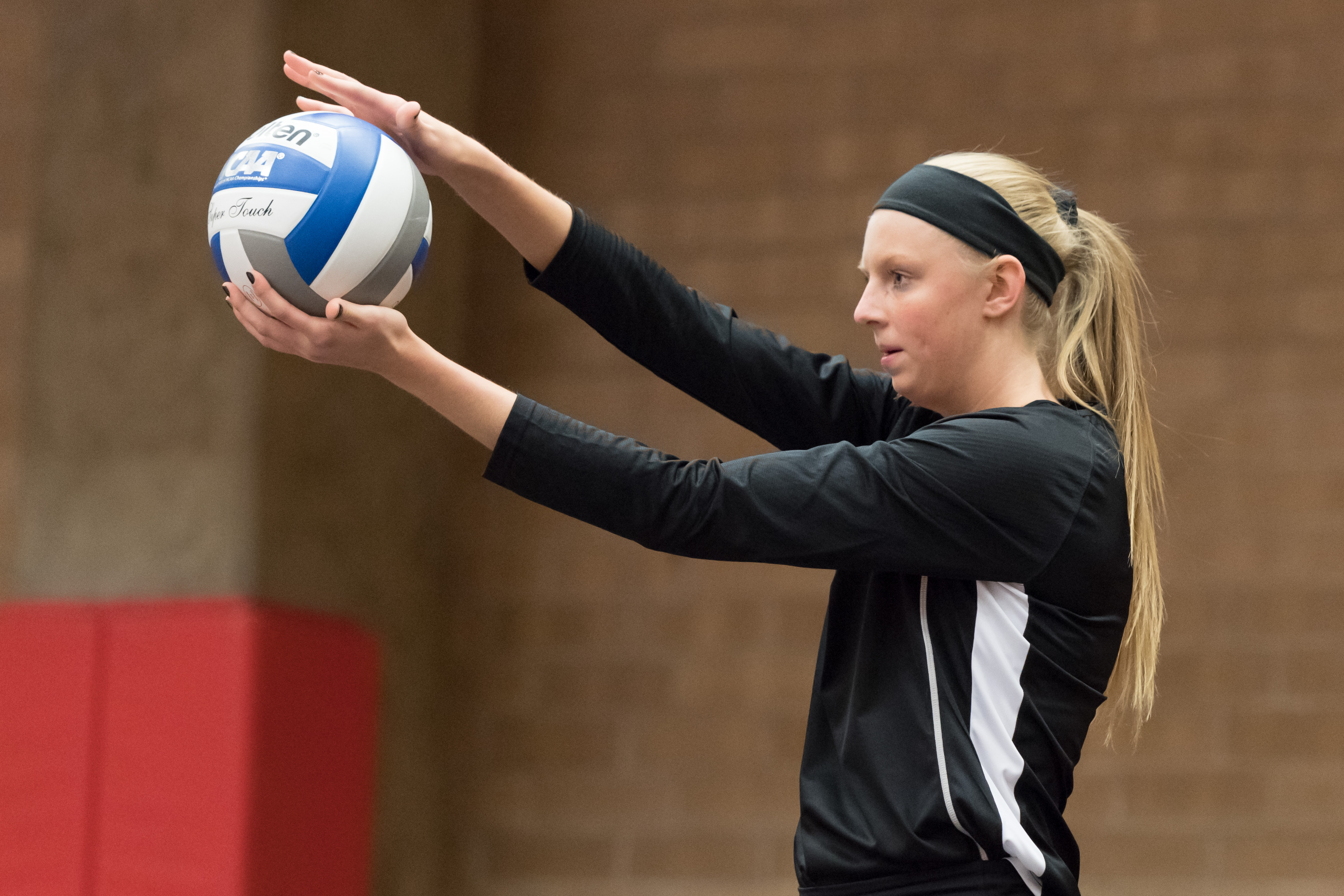 A volleyball player is holding the ball in her hands and is getting ready to hit it.