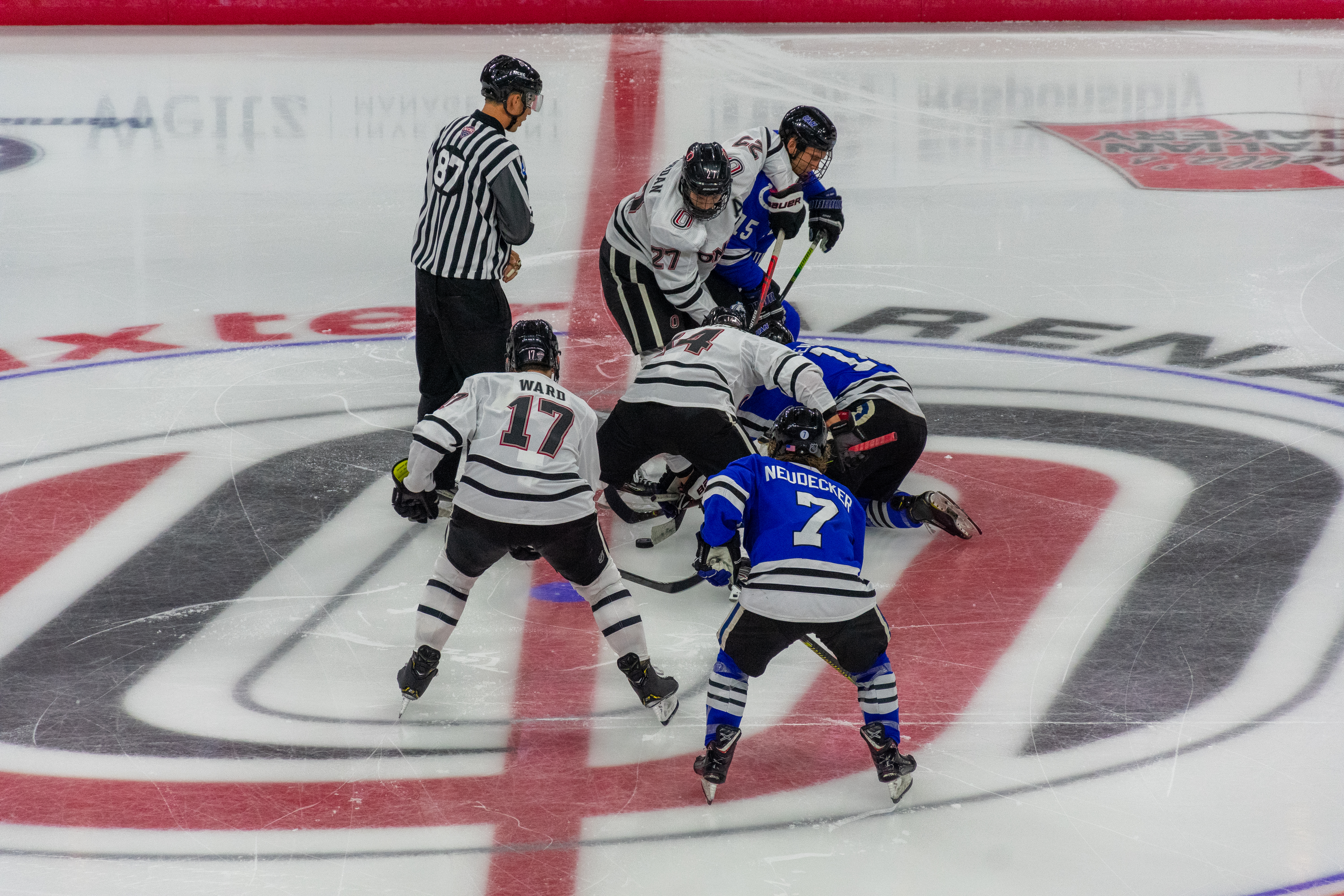 Several hockey players battle for the puck on the ice