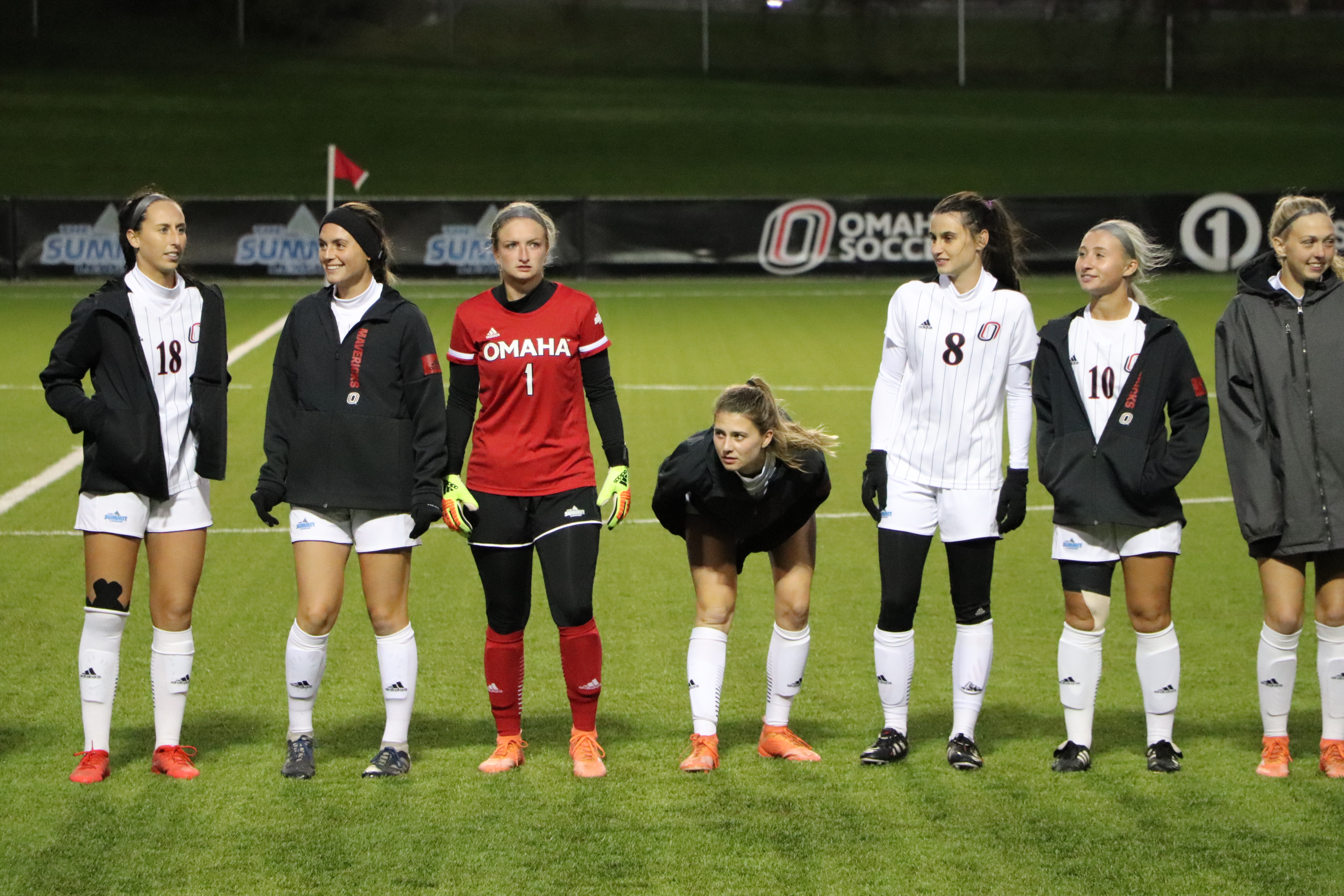 Omaha women's soccer players stand on the field before a match