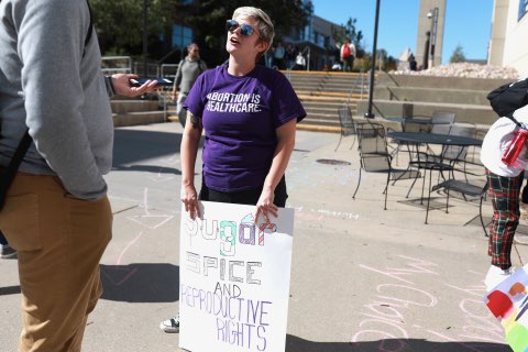 A person holding a sign advocating for reproductive rights