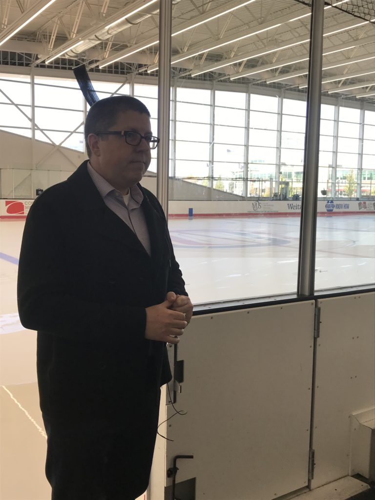 A man is speaking by an ice rink