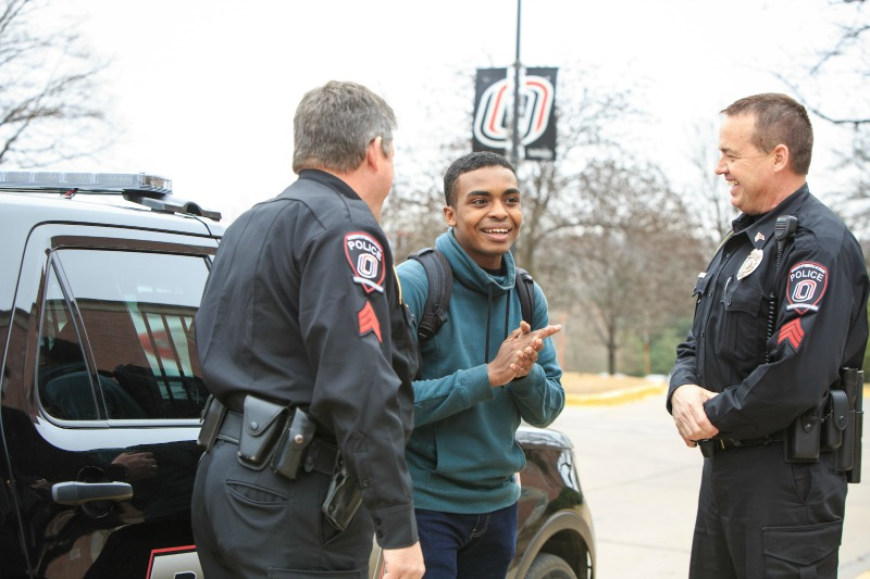 A student chats with UNO police in Elmwood Park.