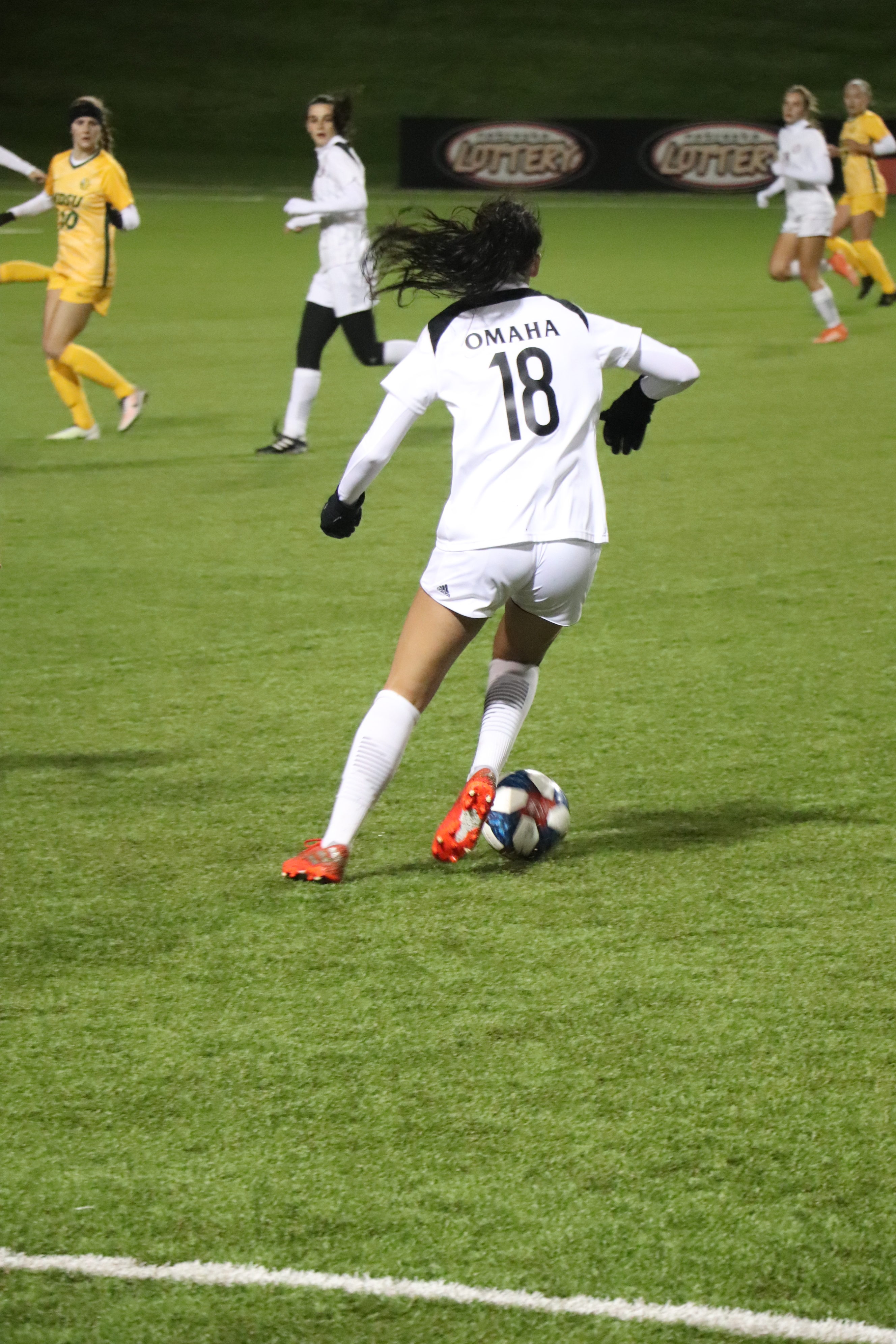 A UNO women's soccer player with the ball at her feet.