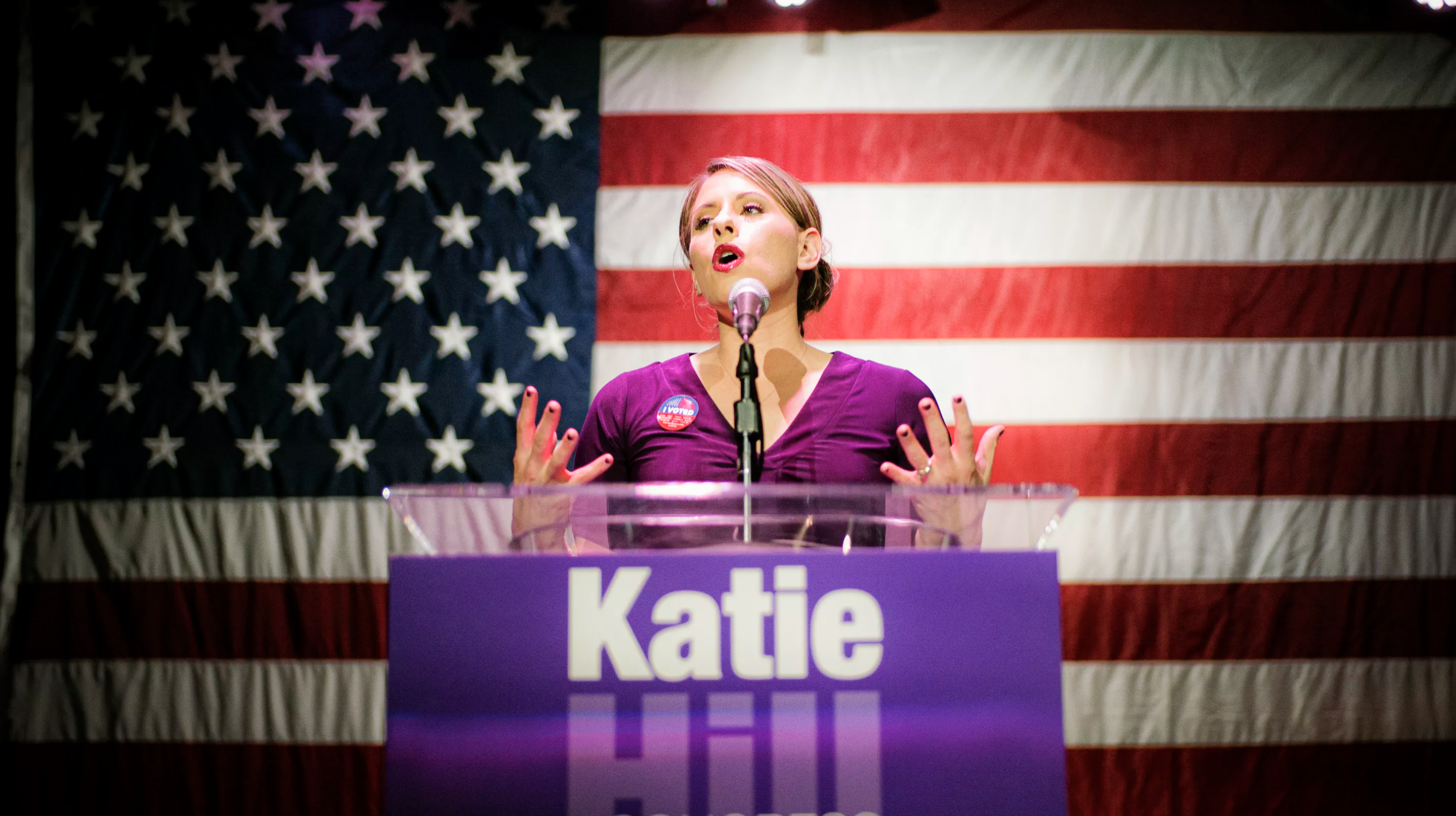 Politician Katie Hill is standing and giving a speech front of an American flag