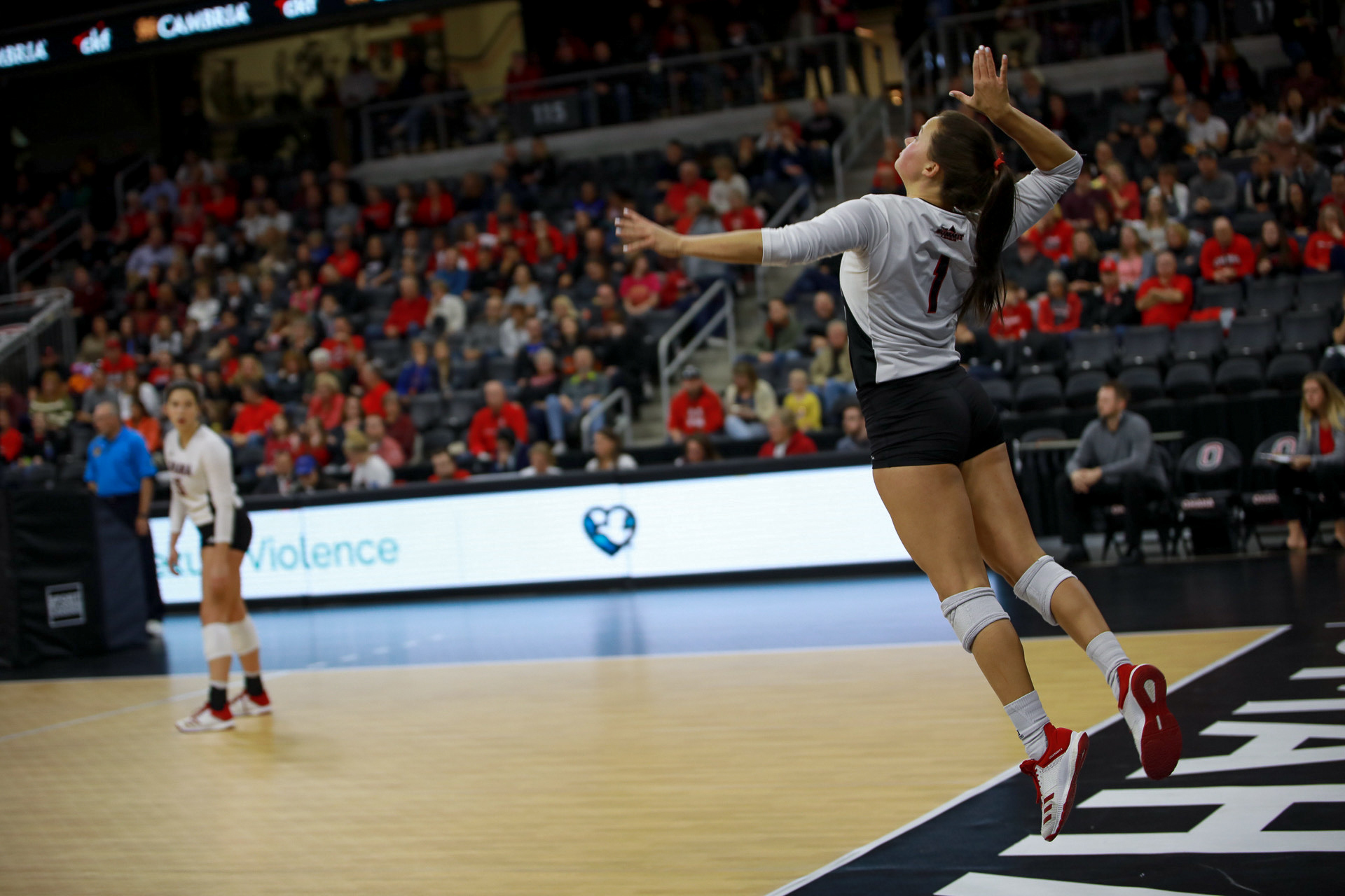 A UNO volleyball player is serving the ball