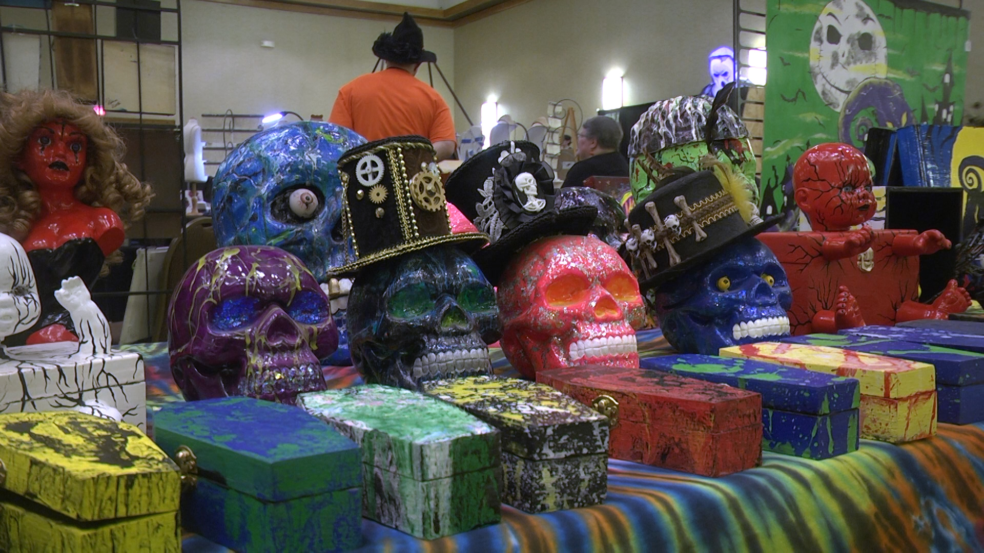 Several decorated skulls and coffins are on display