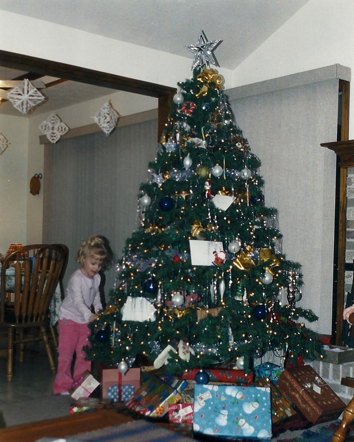 A girl looking at presents under a Christmas tree