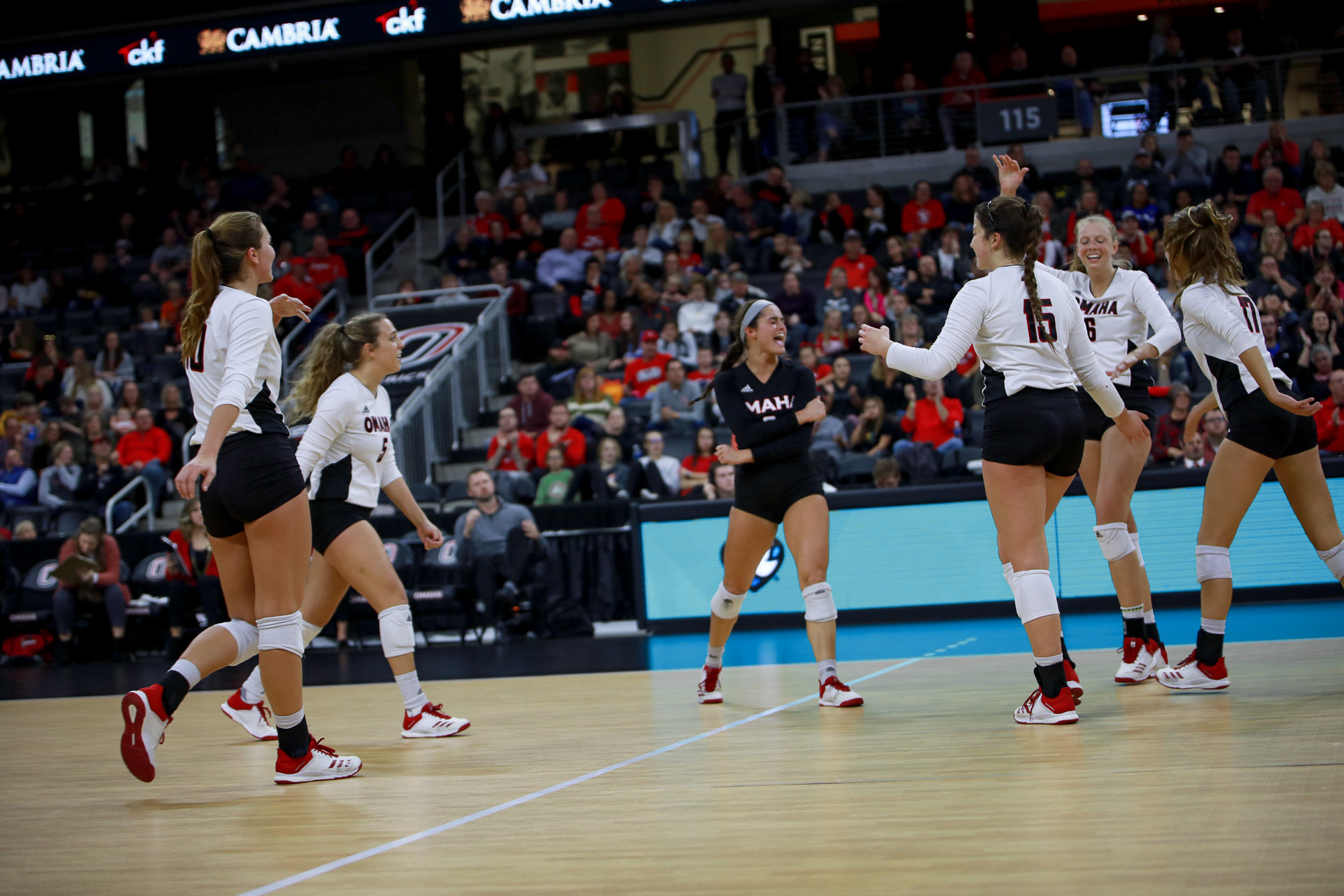 Omaha volleyball players celebrating on the court