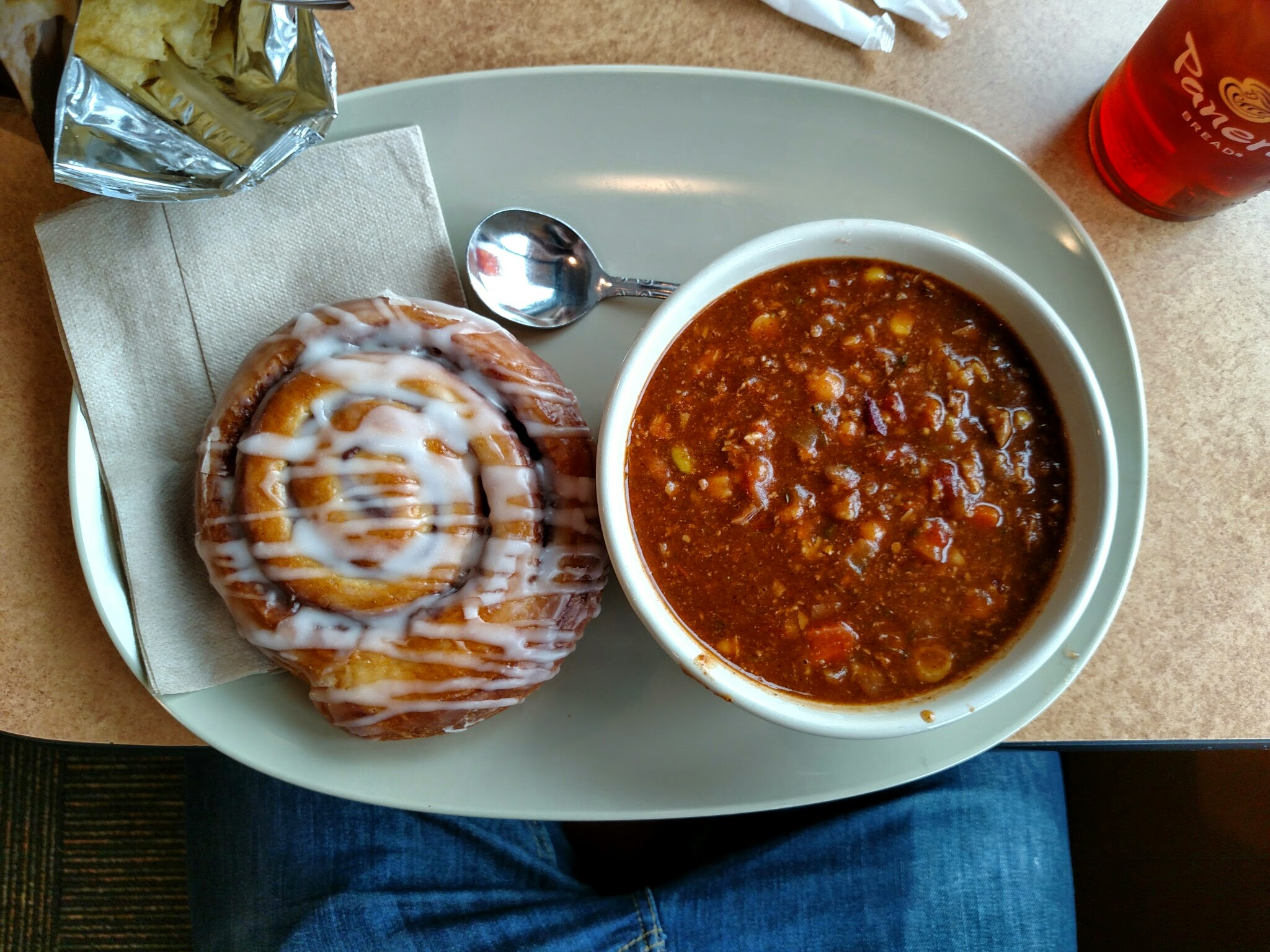 An image of a bowl of chili and a cinnamon roll