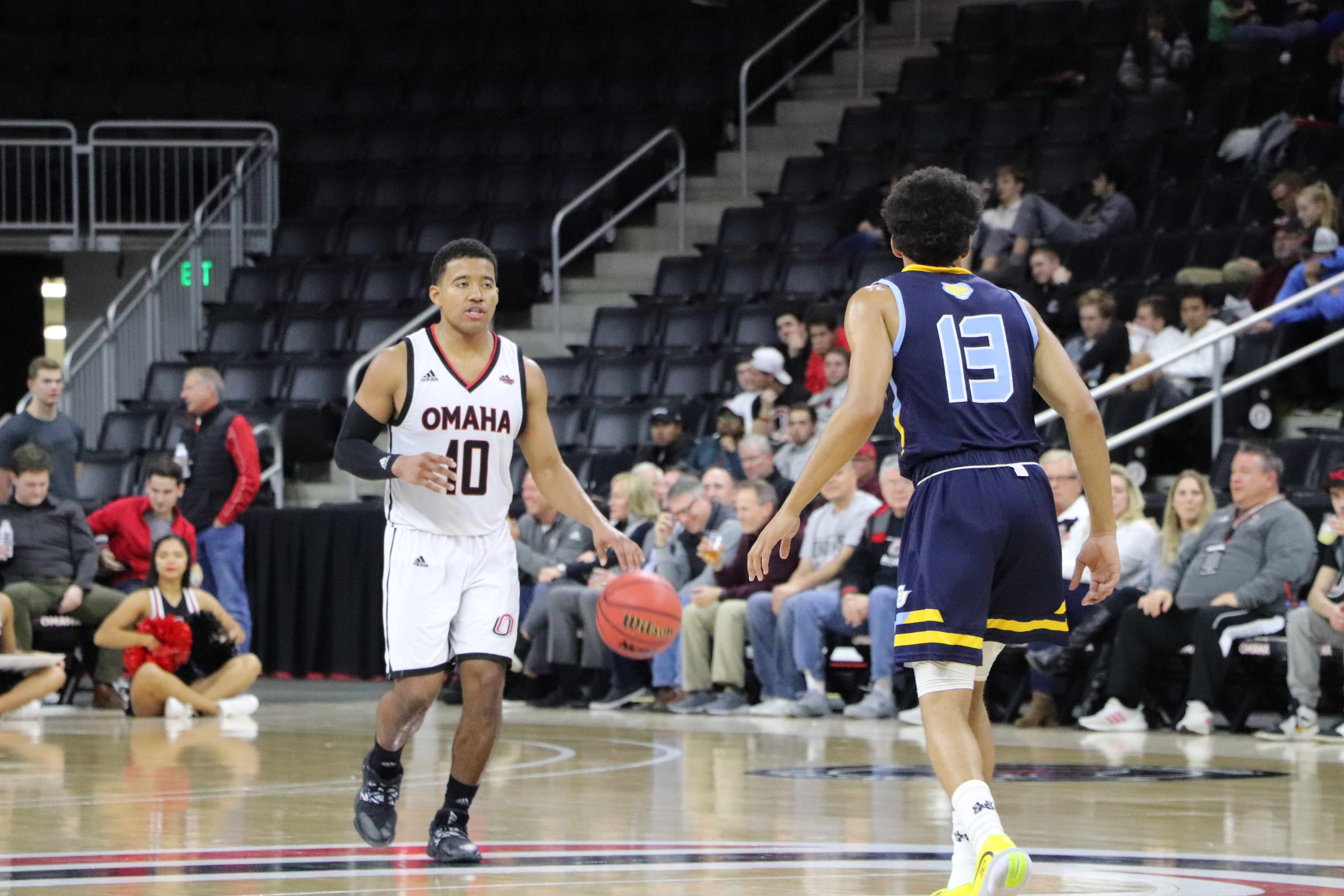 An Omaha basketball player dribbling down the court